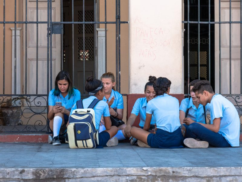 A group of high school students sit in 'el malecon' ( a wall by the Charity Theater) chatting and checking their smartphones. They are wearing the traditional blue uniform
